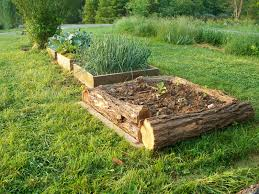 Small Picture Rough hewn logs provide walls for a raised bed while blending in