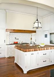 amazing kitchen features walls clad in beadboard trim framing a large kitchen hood with wood trim which is suspended over a subway tiled backsplash with