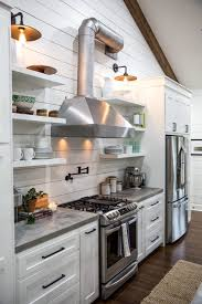 fixer upper kitchen with an industrial feel features a stainless vent hood open shelving and