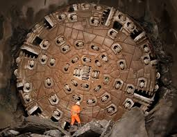 A miner stands in front of the tunnel drilling machine Sissi.