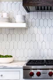 A white kitchen hood with wood trim, flanked by stacked white floating  shelves, stands over a white geometric tiled backsplash, Tabarka Terracotta  Picket ...