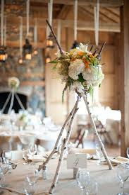 tall birch log centerpieces with white, green and yellow flowers
