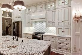 impressive white kitchen design with white patterned kitchen backsplash and chandelier light over kitchen island plus