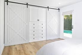 the master bedroom incorporates an ingenious barn door closet system drawers and cabinets provide storage in the center of the wall for folded clothes and
