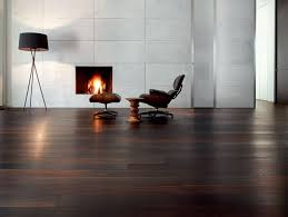 relaxing room with built in fireplace and comfortable swivel accent chair on dark hardwood floor also concrete wall