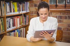 write a career development plan a teacher studies a laptop in a library