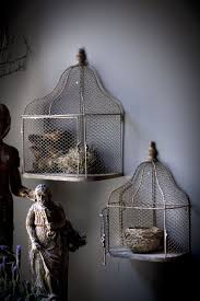 This wall decor is an iron cage with four bird figurines inside. Wall Hanging Metal Bird Cages Bird Cage Decor Hanging Bird Cage Vintage Bird Cage
