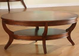 this intricately carved oval coffee table features two thick slab surfaces with a smaller