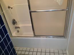 old fiberglass tub shower unit with framed glass doors before new shower installation