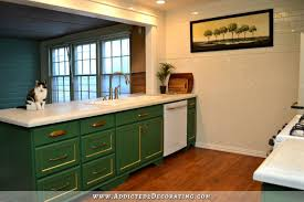 kitchen with kelly green cabinets herringbone subway tile on walls and white concrete countertops