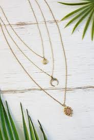 the down memory lane necklace features triple layered gold chains with a round pendant with