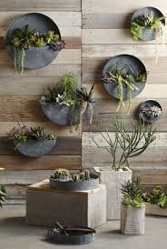 round zinc planters attached to the wall is a cool space-saving idea