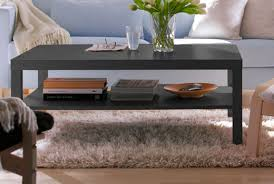 living room side table. lack coffee table in black-brown with shelf, storing books and decorations. living room side