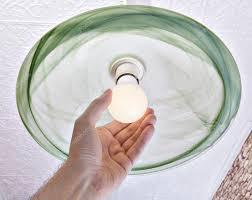 hand twists energy saving led lamp on ceiling light stock photo