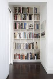 furniture white wooden bookshelves connected by dark brown wooden floor and white wall eye