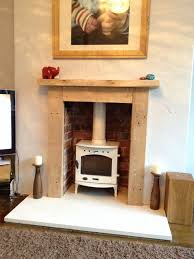 white enamel multi fuel burner limestone hearth and oak surround like the wooden fireplace