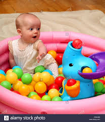 A 6 month old baby girl looks surprised as a ball pops out of the toy elephants trunk