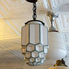 art deco pendant light features a tiered milk glass skyser shade with green trim on brass