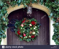 Holly And Ivy Garland Above Front Door With Holly Christmas Wreath