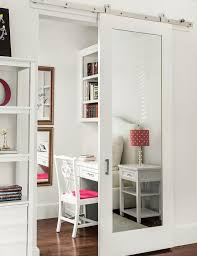chic bedroom features a mirrored barn door on rails opening to a home office