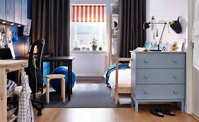 a dorm room with a bed light blue painted chest of drawers desk and