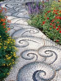 This beautiful cobblestone pathway resembles a winding river flowing  through luscious garden beds on either side