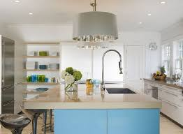 modern two tone kitchen with white perimeter cabinets with beige countertops blue kitchen island with beige countertop and sink with instant hot water