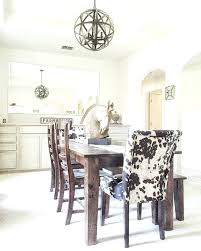 cow print dining chair dining table similar here cow print chairs here chandelier here horse head here farmhouse sign here
