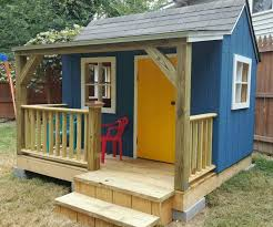 a playhouse with a front porch windows and door