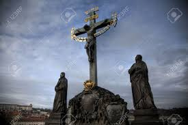 A statue of a cross with hebrew letters on Charles Bridge Prague The Czech Republic Stock