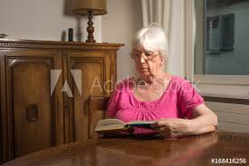 old lady reading in her living room a book