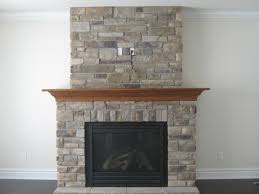 brown wooden mantel shelf over black fire box of grey stone fireplace on white