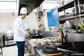 busy kitchen. Chef In Hotel Or Restaurant Kitchen Busy Cooking