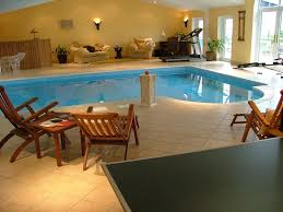residential indoor lap pool. Attractive Residential Indoor Swimming Pools Design Ideas With Cream Tiles Flooring And Wooden Lounge Chairs Plus L Shape Pool Also Cozy White Sofa Complete Lap