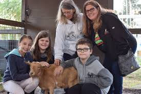 Do Good Farm opens food store in Winter Garden - Noah, Abby and Wendi  Williams, Cameron Taylor and Sandy Mummaw spend time in side the goat  enclosure to pet one of the