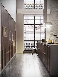 white kitchen windowed partition wall: this kitchen is decadent the warm woods pop against those tall white walls and that huge window and the finishes are super chic