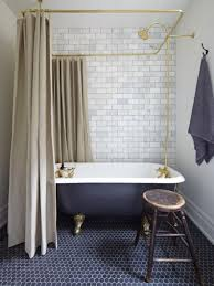 above small dark blue floor mosaics with marble wall subway tiles brass fixtures image via