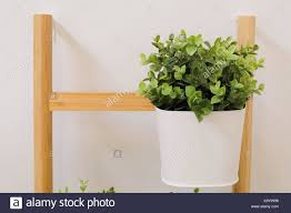 office flower pots. Artificial Green Plants In A White Metal Flower Pots Stand On The Wooden Shelves, For Home And Office Decoration Without Care. S