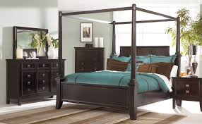 Black Wood Canopy Bed Frame With Headboard And Blue Bedding Set On ...