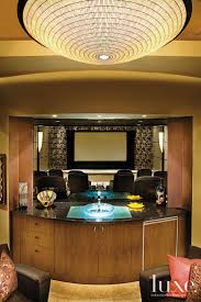This contemporary bar area looks out to the home theater through bent glass.