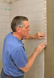 a band of smaller border trim tiles add visual interest to this shower wall