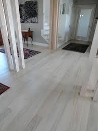 elegant laminate grey wood floors with white wooden pillars as well as single frosted main door