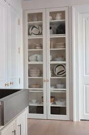 dining table leaf hardware: cabinets with glass paneled doors and interior lighting create the illusion of a window giving the space an open airy feel the glass fronted dish closet