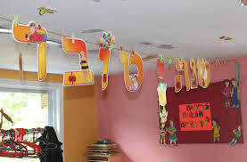 letters in hebrew hanging at the entrance to gan gurim spell out the greeting for a happy jewish new year ben s jta