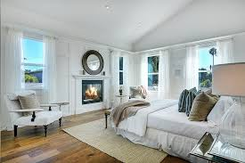 big master bedrooms couch bedroom fireplace: this mostly white master bedroom has multi toned hardwood floors and a simple natural fiber