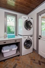 laundry room marked by its stained dutch door, window, herringbone brick  paver flooring and a stacked front loading washer and dryer, laundry bins,  ...