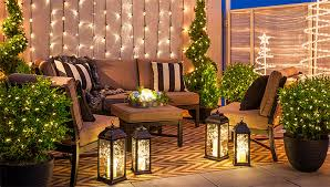 Outdoor Christmas lighting on balcony with white string lights, lanterns,  spiral trees and lighted