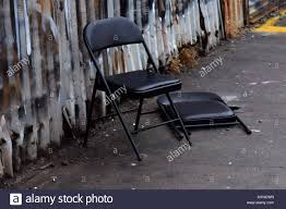 black metal folding chairs. Black Metal Folding Chairs On A Dirty White Sidewalk In Front Of Rusty Wall.