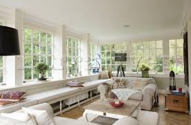 Uncurtained sun room with long window seat in Surrey home UK
