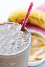 a closeup of a chocolate peanut er smoothie in a gl with a pink striped paper